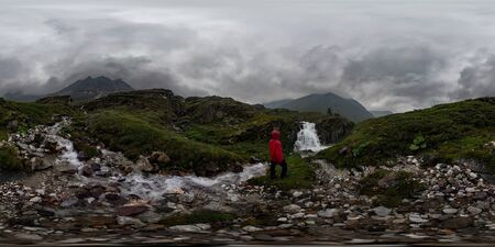 man in red stands under waterfall on black rock in mountains on cloudy rainy day. Spherical panorama 360vr