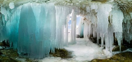 Blue Ice cave grotto on Olkhon Island, Lake Baikal, covered with icicles. Wide panorama