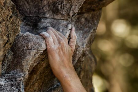 Closeup view of rock climbers hand gripping hold on natural cliff Stock Photo