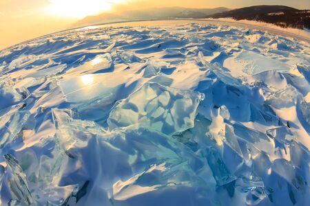 Transparentes blaues Toros-Baikal-Eis scheint durch den rissigen Sonnenuntergang