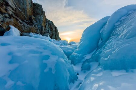 ice rock of the winter lake Baikal opposite the rocky mountain of Olkhon Island.