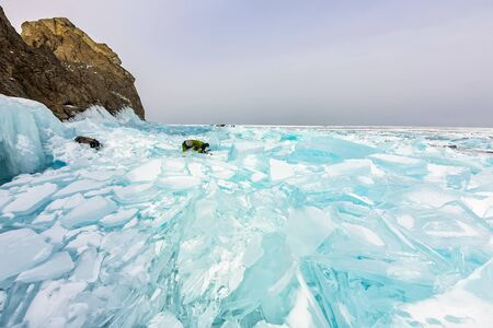photographer takes pictures frozen clear ice in winter lake baikal, russia