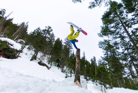 Snowboarder freerider standing on a dry log in a jump from a snow ramp in a background of forest and mountains. Zdjęcie Seryjne