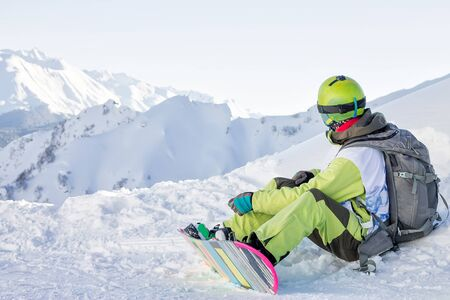 snowboarder freerider sits on a slope and fastens his snowboard while looking at the mountains. Russia Sochi Rosa Khutor Banco de Imagens