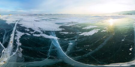 Ice crack at sunset in the ice of Lake Baikal at the on Olkhon Island. Cylindrical panorama 360.