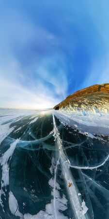 Cape with a cave at sunset in the ice of Lake Baikal at the on Olkhon Island. Vertical wide panorama