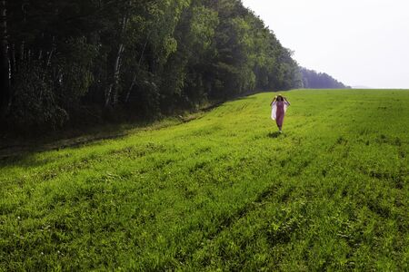 young girl in a pink dress walks in a green field along the forest trees.