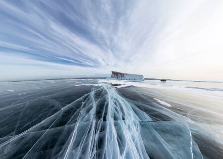 Ice of Lake Baikal in cracks near the island at sunset under gray clouds. Wide panorama