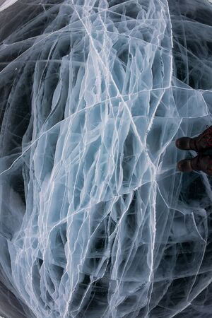 The gray ice of Lake Baikal in many white cracks near the background graphic resource Foto de archivo