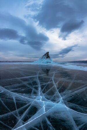 Ice of Lake Baikal in cracks near the island of Elenka at sunset under gray clouds. Wide panorama Foto de archivo