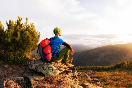 Hiker with backpack sitting on a rock by a tree against the background of dawn.