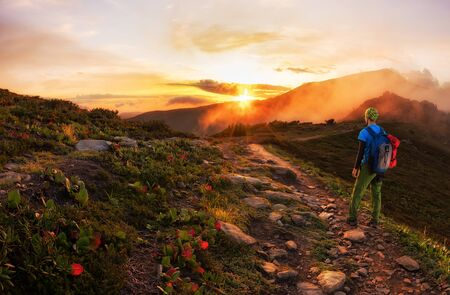 Hiker with backpack walking along a mountain trail in the background of dawn.