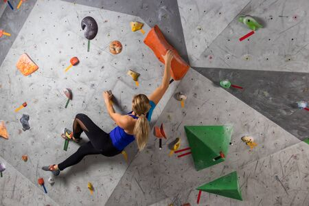 Rock climber woman hanging on a bouldering climbing wall, inside on colored hooks.