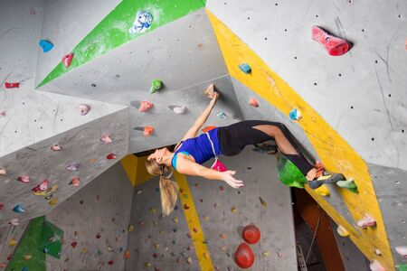 Rock climber woman hanging on a bouldering climbing wall, inside on colored hooks Foto de archivo