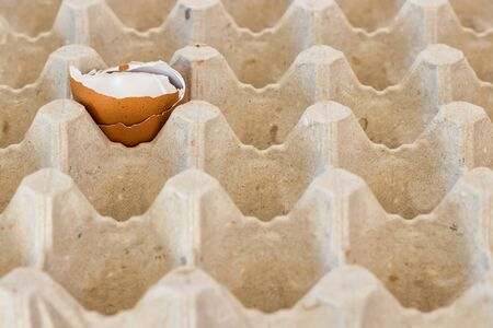 box with broken eggshell brown chicken eggs, background texture pattern