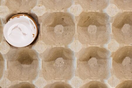 Flat view of a box with broken eggshell brown chicken eggs, background texture pattern Foto de archivo