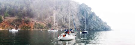 yachts are anchored off a rocky shore in a foggy morning floats on the sea. Wide panorama.