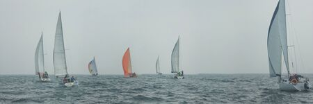 Yacht regatta at sea during the rain and orange sail in a foggy morning floats on the sea. Wide panorama.