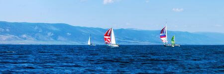 Yacht regatta with an color sail in a foggy morning floats on the sea. Wide panorama. Foto de archivo