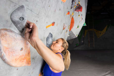 Rock climber woman close-up hanging on a bouldering climbing wall, inside on colored hooks.