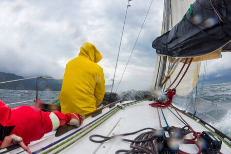 Motion blur men work with cord of sails of a yacht in the difficult storm sea. Present mans sports it yachting