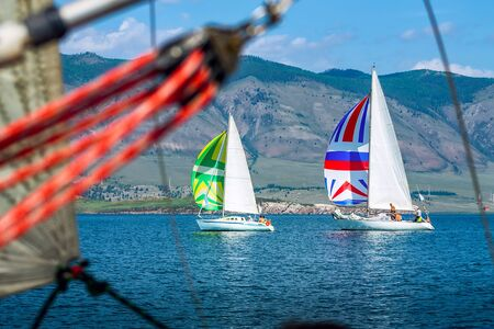Yacht regatta with an color sail against the green slopes of the mountains on the sea. Wide panorama