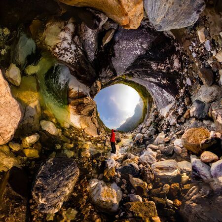 man in red stands under a waterfall on rock in the mountains on sunset. Tiny little planet 360 Фото со стока