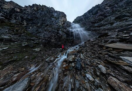 man in red stands under a waterfall on a black rock in the mountains on a cloudy rainy day