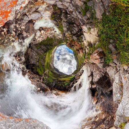 waterfall water of a mountain lake under a blue sky in the clouds. sand beach. Tiny little planet 360 Фото со стока