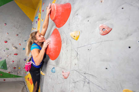 Rock climber woman hanging on a bouldering climbing wall, inside on colored hooks Фото со стока