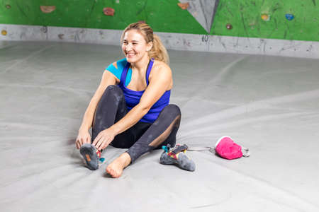 Rock climber woman sitting takes off rocky shoes on a bouldering climbing wall holl, inside on colored hooks Фото со стока