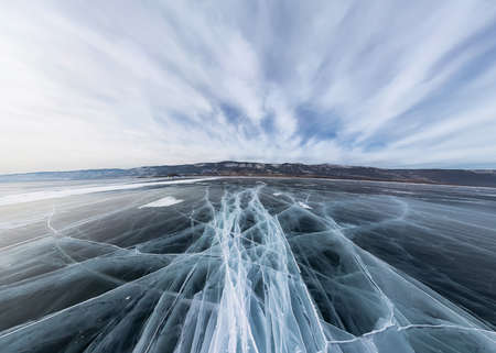 Ice of Lake Baikal in cracks near the island at sunset under gray clouds. Wide panorama Foto de archivo - 152027303