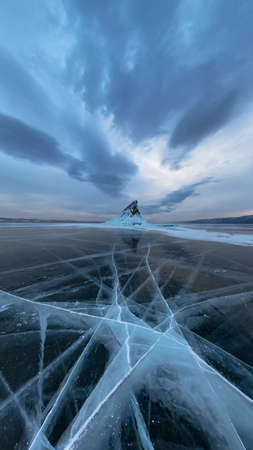 Ice of Lake Baikal in cracks near the island of Elenka at sunset under gray clouds. Wide panorama Фото со стока