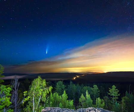 Neowise comet in the starry sky over the forest with city lights on the background