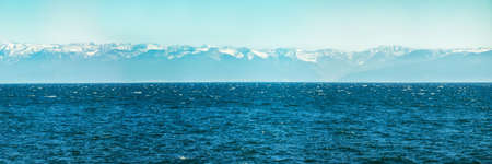 Panorama of blue water of Lake Baikal, with mountain peaks against the sky of summer Фото со стока