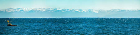Panorama of blue water of Lake Baikal, with mountain peaks against the sky with a tree in the middle of summer Foto de archivo - 155930013