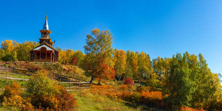 Wooden temple on Lake Baikal in the yellow trees of the autumn forest. Panorama Russia
