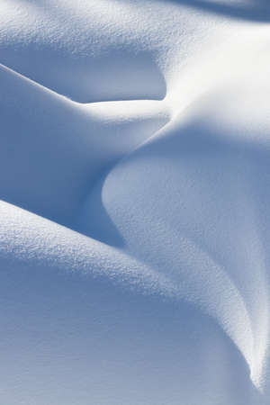 beautiful smooth lines texture of snowdrifts play of light and shadow of a winter landscape on the background Фото со стока