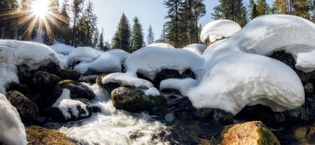 Waterfall on the river in winter among snowdrifts in a mountain forest. Фото со стока