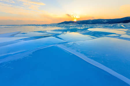 Transparent blue hummocks Baikal ice is shining through the crack sunset Фото со стока