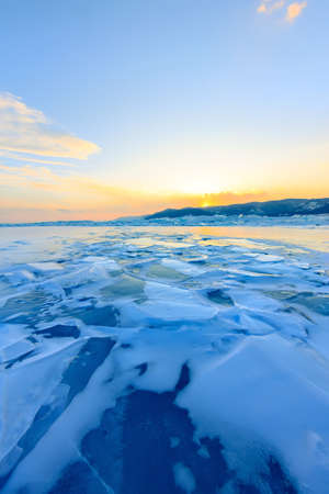 Transparent blue hummocks Baikal ice is shining through the crack sunset Foto de archivo - 158912273