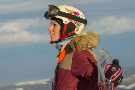 portrait of a snowboarder woman freerider in helmet in snowy mountains
