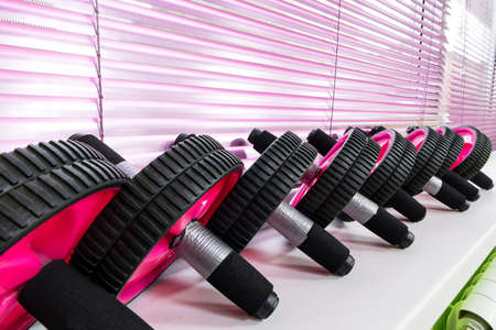 Close-up of a row of AB wheels on a light background on the shelf of a fitness gym Фото со стока