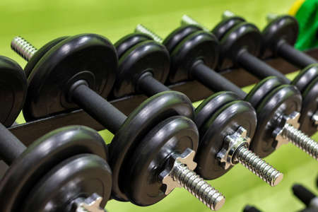 dumbbell set close-up on rack in sport fitness gym center workout training and concept healthy sport equipment and tool theme Фото со стока