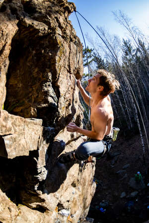 male climber with a naked torso climbs onto a rock with top insurance Foto de archivo