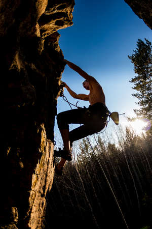 male climber with a naked torso climbs onto a rock with top insurance Foto de archivo - 159674056
