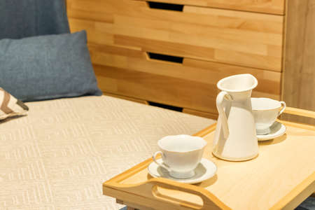 wooden tea table stands on the bed with cups. Bed with pillows and blue duvet and wooden chest of drawers