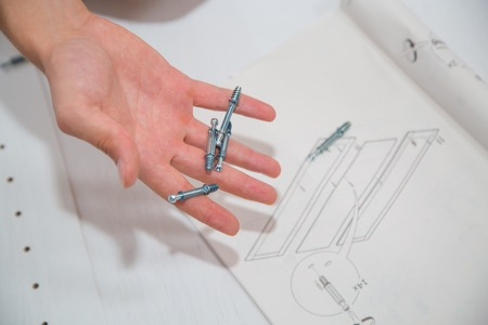 Screw-bolts and nuts in hand of man on the drawings background photo