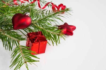 branche sapin noel: Gros plan d'une branche d'arbre de No�l et la d�coration de couleur rouge sur fond blanc