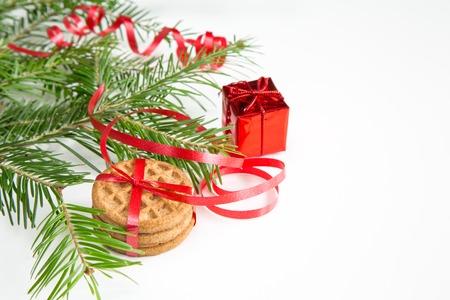 branche sapin noel: Gros plan de la branche de l'arbre de No�l, les cookies et la d�coration de couleur rouge sur fond blanc